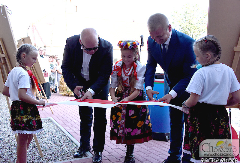 dziewczynki trzymają wstęgę, którą przecinają (od lewej) burmistrz Choszczna Robert Adamczyk, Amelia Leśniańska i radny Krzysztof Połomski z okazji otwarcia świetlicy w Raduniu