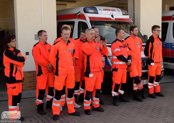 Na zdjęciu widać ratownikow pogotowania, którzy stoją przed ambulansem