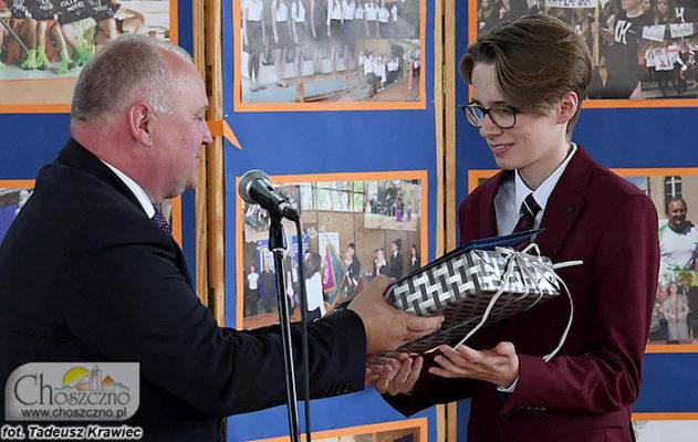 burmistrz Robert Adamczyk wręcza prezent dla najlepszego ucznia kończacego gimnazjum Jerzego Ciecierskiego