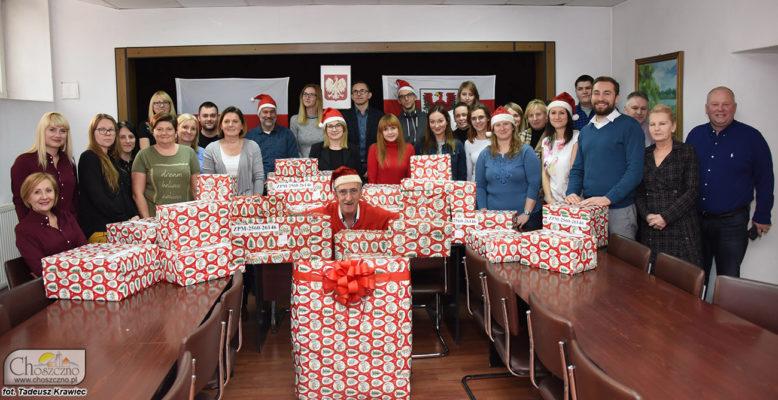 na zdjęciu są pracownicy urzędu, a przed nimi czerwone paczk