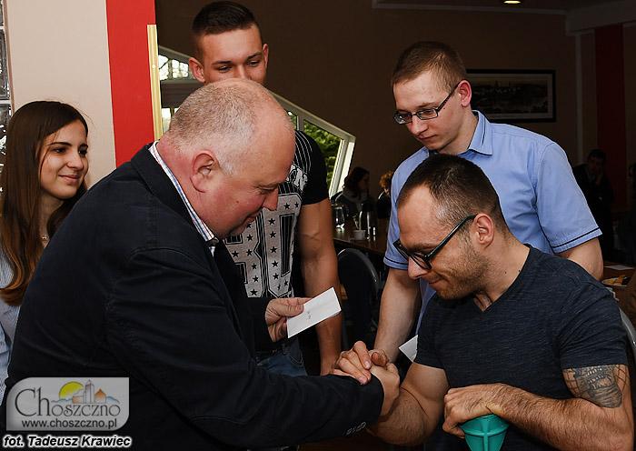 burmistrz Robert Adamczyk wręcza sypednia sportowe