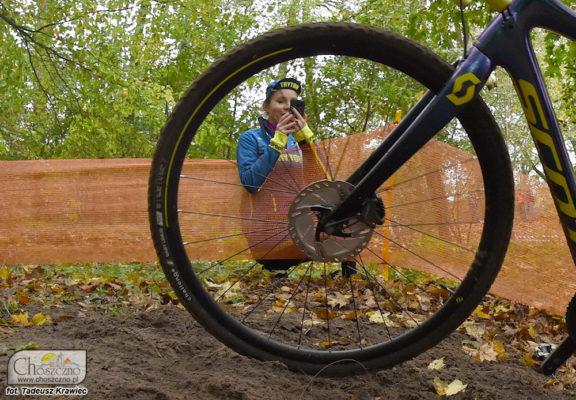dzewczynka robi zdjęcie kolarzom ujęcie przez koło od roweru
