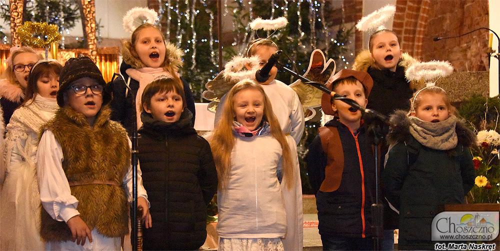 zdjęcie orzedstawia przebrane zdjęcie za aniołki i pasterzy, które śpiewają kolędy